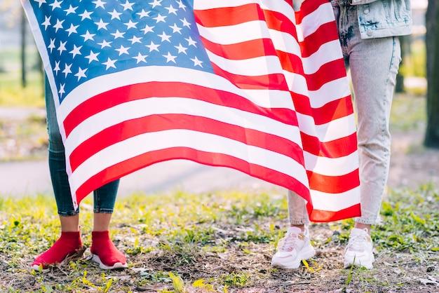 Mulheres irreconhecíveis, segurando a bandeira do eua em quatro de julho