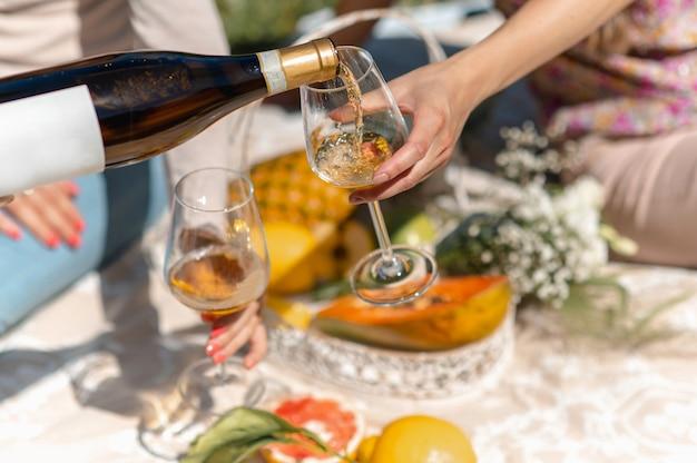 Mulheres irreconhecíveis sentadas em um cobertor fazendo piquenique. mulher derramando vinho branco em um copo. fruta tropical no fundo