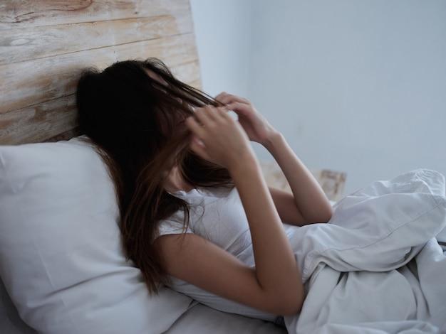 Mulheres já estão na cama segurando seus cabelos closeup insatisfação