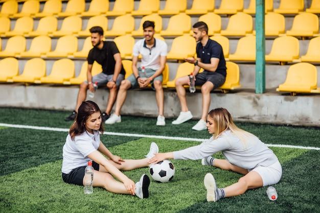 Mulheres jogadoras de futebol alongando os músculos da perna se preparando para a partida no estádio