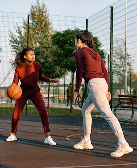 Mulheres jogando juntas um jogo de basquete