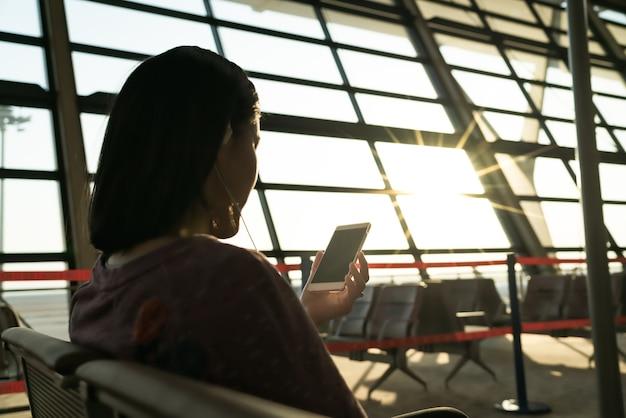 Mulheres jovens à procura de informações enquanto espera voando na janela do aeroporto