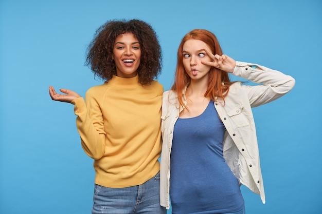 Mulheres jovens adoráveis e alegres, mantendo as mãos levantadas em pé sobre uma parede azul, abraçando-se enquanto se divertem juntas e de bom humor