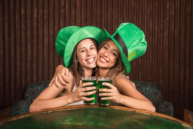 Mulheres jovens alegres abraçando com copos de bebida no sofá perto de mesa