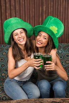 Mulheres jovens alegres abraçando e batendo copos de bebida no sofá