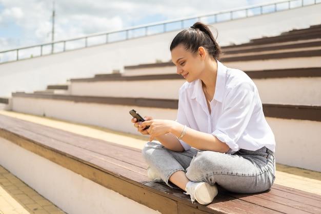 Mulheres jovens alegres felizes com smartphone, aproveitando o dia de sol sentado no anfiteatro.