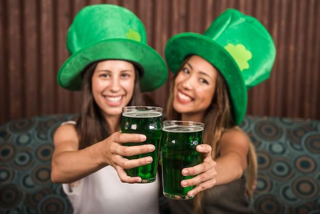 Mulheres jovens alegres mostrando copos de bebida no sofá