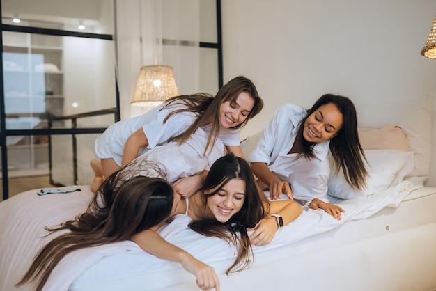Mulheres jovens amigas positivas dentro de casa, na cama, na festa das despedidas de solteiro em casa