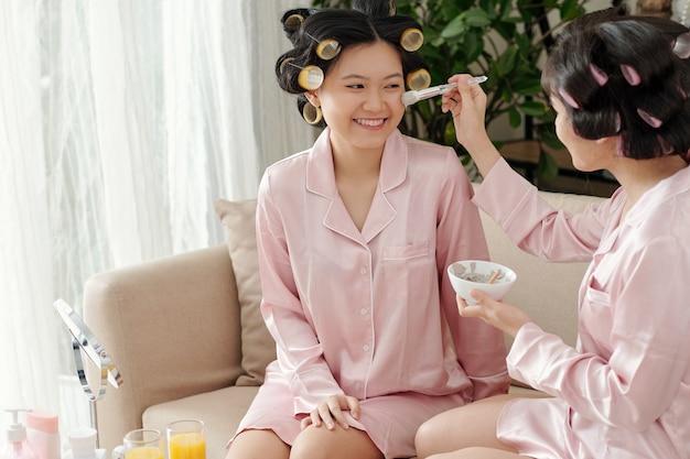 Mulheres jovens aplicando máscara de argila para minimizar os poros nos rostos umas das outras
