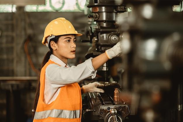 Mulheres jovens atendem trabalhador feliz trabalhando em engenheiro de trabalho de fábrica de metal consertar máquina de indústria pesada de manutenção.