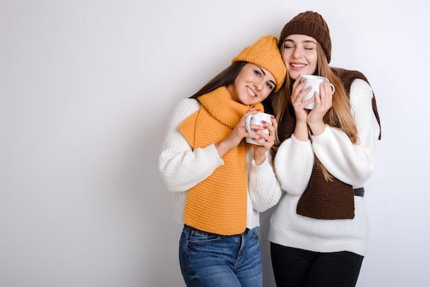 Mulheres jovens atraentes alegres em lenços quentes em pé e segurando uma caneca branca com chá quente sobre fundo cinza