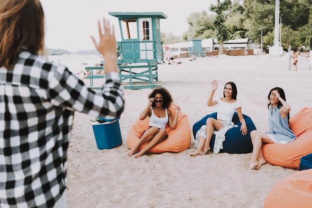 Mulheres jovens atraentes na festa de praia de cadeiras de saco