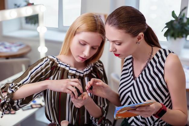 Mulheres jovens bonitas juntas enquanto testam novos cosméticos