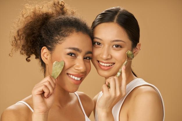 Mulheres jovens bonitas sorrindo para a câmera usando o rolo de jade e o gua sha facial enquanto posam
