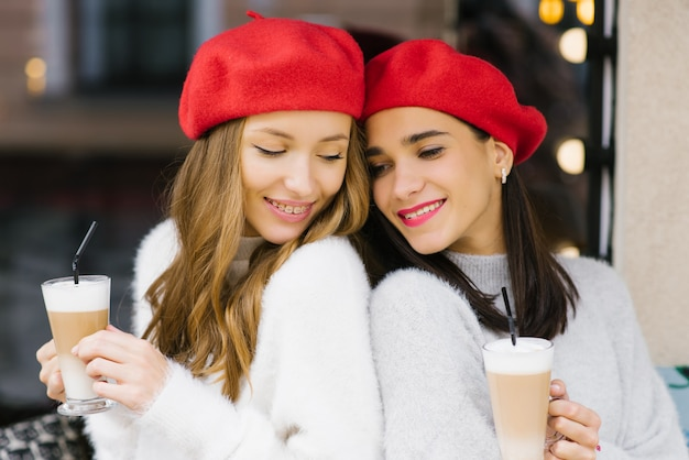 Mulheres jovens bonitos em boinas segurando canecas de café nas mãos