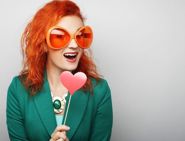 Mulheres jovens brincalhões segurando um coração de festa e óculos.