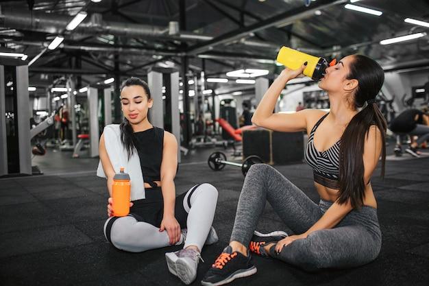 Mulheres jovens calmas e pacíficas sentam-se no chão no ginásio. o modelo novo asiático olha para baixo na garrafa de água alaranjada. sua amiga bebe da amarela. eles sozinhos na academia.