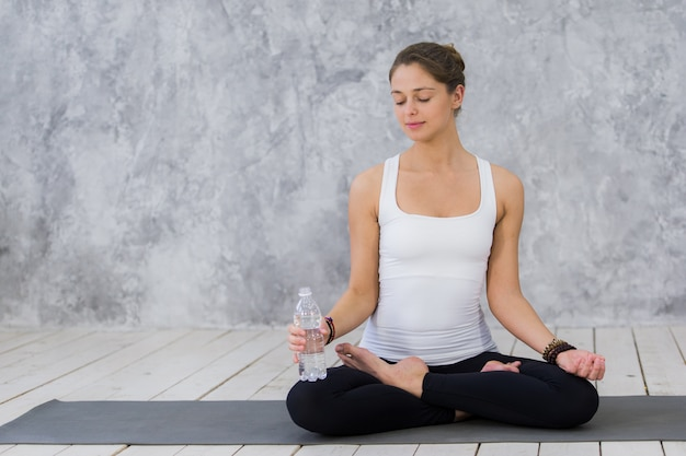 Mulheres jovens cansadas em esportes roupas água potável enquanto está sentado no colchonete