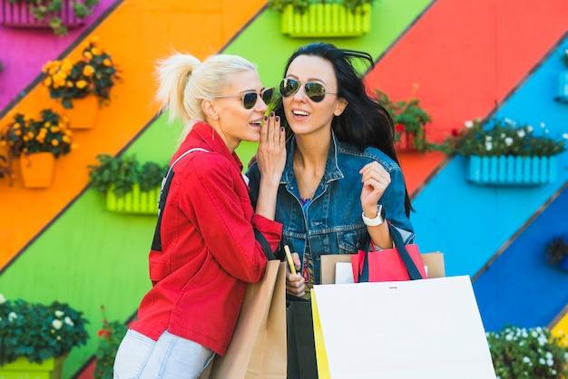 Mulheres jovens, com, bolsas, falando, perto, parede