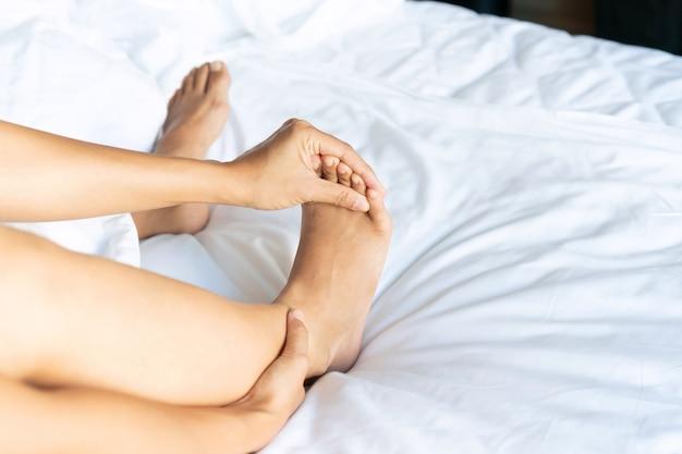Mulheres jovens com cãibras nos pés pela manhã