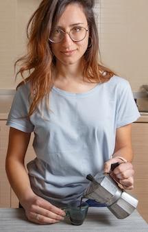 Mulheres jovens com camiseta azul ficam na cozinha em casa com cafeteira moka