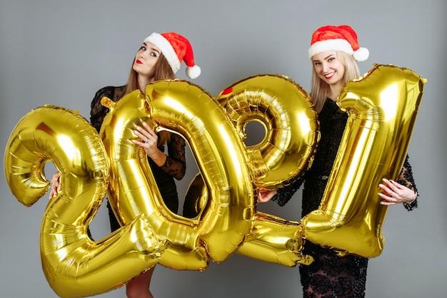 Mulheres jovens com chapéus de papai noel segurando balões dourados