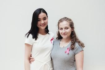 Mulheres jovens com fitas cor de rosa