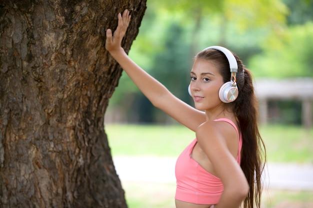 Mulheres jovens com fone de ouvido aguardando tanque de árvore