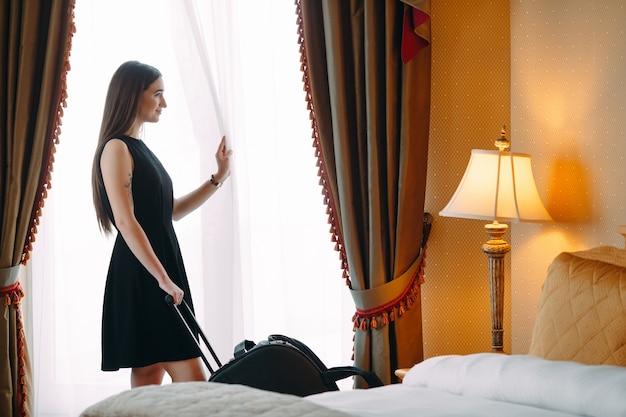 Mulheres jovens com mala estão ficando em um quarto de hotel