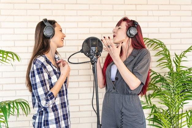 Mulheres jovens com os olhos fechados gesticulando e cantando no microfone enquanto ouvem música em fones de ouvido em um estúdio profissional leve