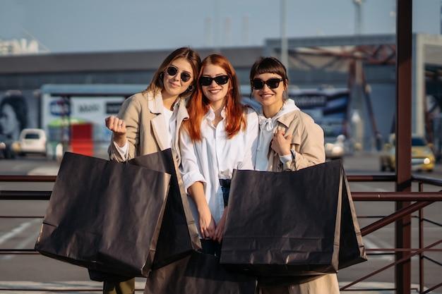 Mulheres jovens com sacolas de compras em um ponto de ônibus posando