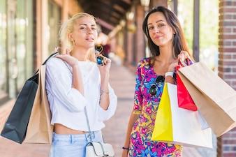 Mulheres jovens, com, sacolas, ligado, rua comercial