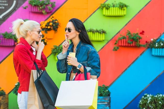 Mulheres jovens, com, sacolas, mostrando, silencioso, perto, parede
