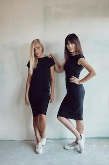 Mulheres jovens com vestido preto na parede