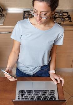 Mulheres jovens de óculos e camiseta azul usando celular e laptop na cozinha