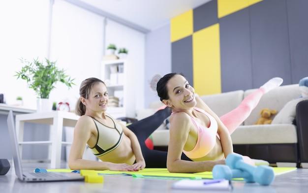 Mulheres jovens deitadas em esteiras de ginástica e balançando os músculos das coxas
