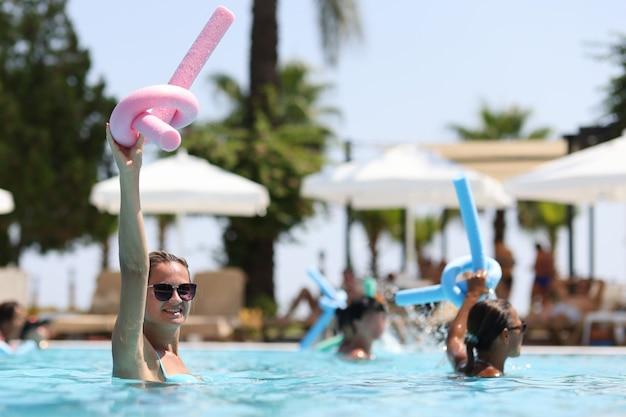 Mulheres jovens durante aulas de hidroginástica em esportes de piscina de hotel