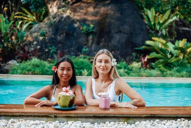 Mulheres jovens e alegres na piscina com coquetéis naturais olham para a câmera e sorriem. recreação e viagem na tailândia.
