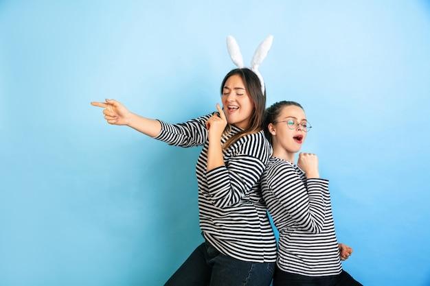 Mulheres jovens e emocionais isoladas na parede azul do estúdio