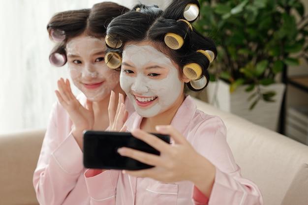 Mulheres jovens e sorridentes felizes tirando selfie com máscara facial de argila e rolos de cabelo