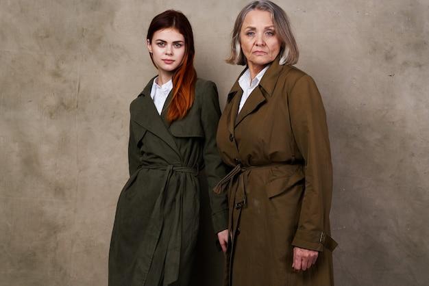 Mulheres jovens e velhas ficam lado a lado fundo isolado estúdio de moda outono. foto de alta qualidade