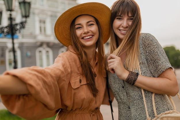 Mulheres jovens elegantes viajando juntas pela europa usando vestidos e acessórios da moda para a primavera