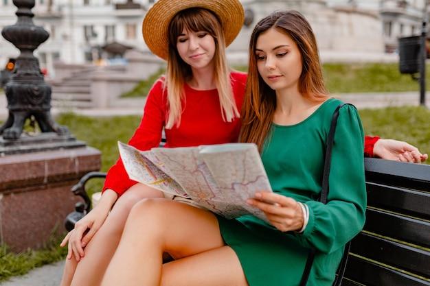 Mulheres jovens elegantes viajando juntas, vestidas com roupas da moda de primavera e acessórios, se divertindo segurando um mapa
