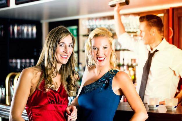 Mulheres jovens em bar ou clube, o barman está misturando coquetéis