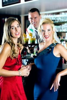 Mulheres jovens em bar ou clube, o barman serve coquetéis