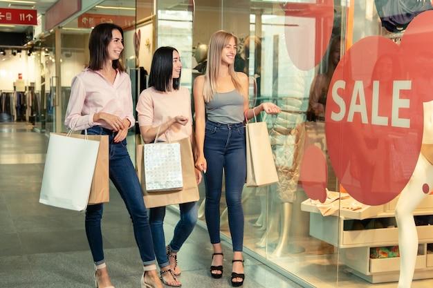 Mulheres jovens em compras no shopping segurar sacolas de compras nas mãos
