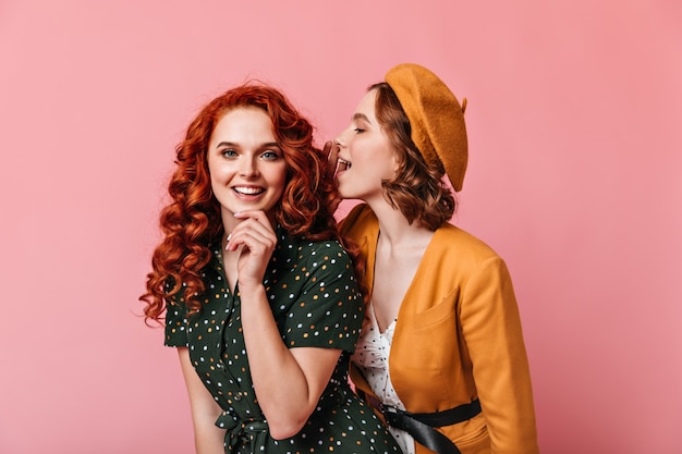 Mulheres jovens em êxtase falando sobre fundo rosa. foto de estúdio de dois amigos em roupa vintage.