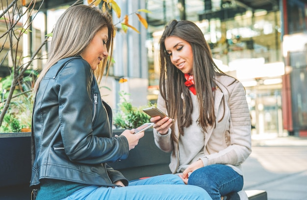 Mulheres jovens em pé em uma área urbana, conectando-se com o telefone móvel esperto na cidade ao ar livre