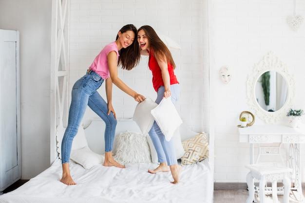 Mulheres jovens em pé na cama em casa
