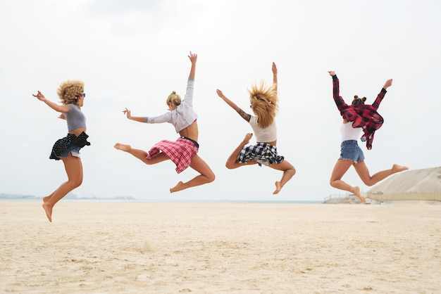 Mulheres jovens em roupa de moda verão pulando na água